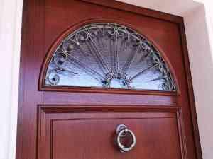 Portone d'ingresso in legno massello di Roveretinto noce con grata in ferro battuto e vetro stile cattedrale