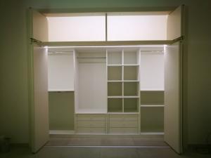Realizzazione e installazione di cabina armadio in legno su misura con laccatura biancacon ante tamburate scorrevoli  a pacchetto su binario