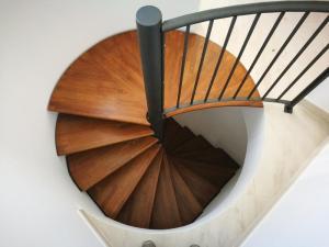 Realizzazione su misura di scala a chiocciola da interno con struttura metallica e gradini in legno taglio laser e ferro battuto